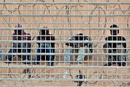 African asylum seekers waited on the Egyptian side of the border fence with Israel in early September. The trip for those trying to cross from Egypt to Israel has become increasingly dangerous as criminal gangs in Sinai have taken migrants and asylum seekers hostage.